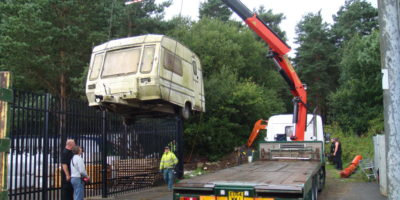 Traveller caravan being lifted onto a lorry by a crane