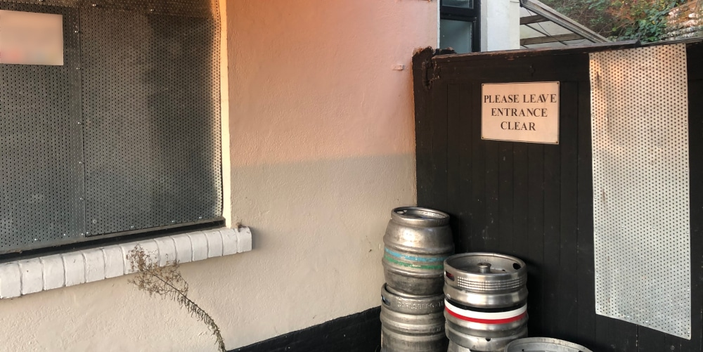 Beer barrels left beside a vacant public house which could enable illegal entry.
