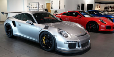Silver, red and blue Porsche's on display in a car showroom